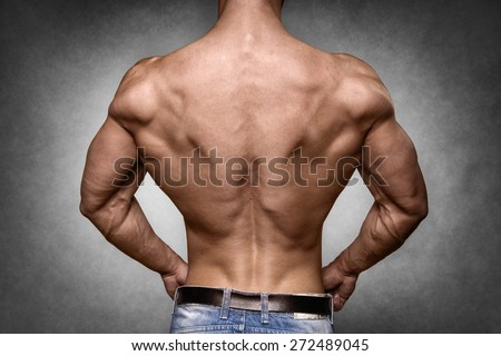 Back of a young man with well trained body, triceps, lats and rhomboid muscle and wearing a denim trousers