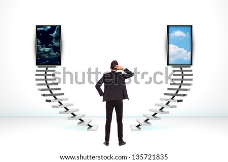 back of an undecided young business man standing with his hand on his head and thinking what to do - stock photo