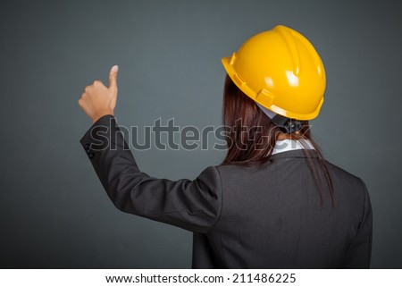 Back of Asian engineer girl show thumbs up on gray background