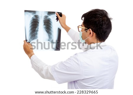 Back of Asian male doctor wear mask look at x-ray film  isolated on white background - stock photo