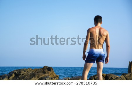 Back of athletic young man shirtless standing on rock against the sky, by the sea or ocean - stock photo