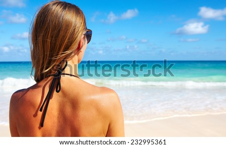 Back of beautiful girl in bikini  on tropical beach - stock photo