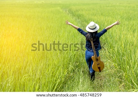 Back of beautiful young women with a guitar in the rice fields .