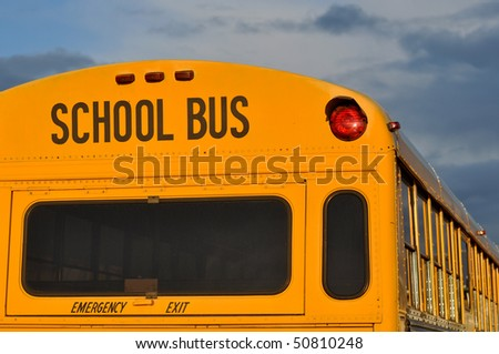 Back of Black and Yellow School Bus with cloudy Sky - stock photo