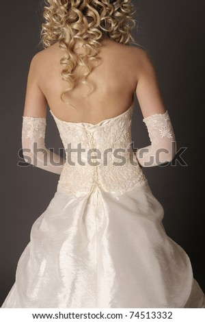 Back of bride in wedding dress on a gray background.