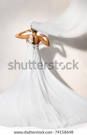 Back of bride in white elegance wedding dress with loop. Long flying veil. Hands raised up. Full length. - stock photo