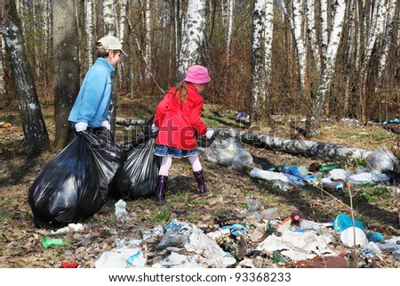 Back of brother and sister with black bags collect trash in park at spring - stock photo
