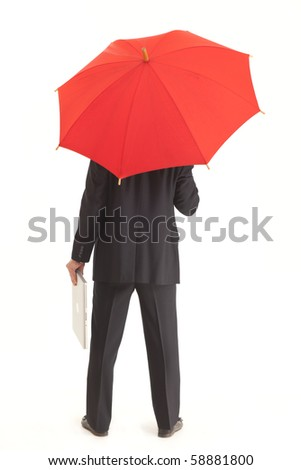 Back of businessman with red umbrella holding a laptop