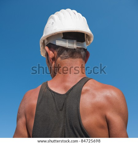 Back of construction worker against blue sky