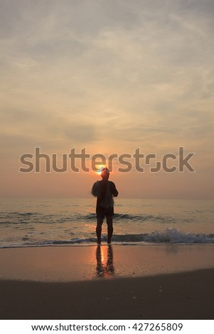 Back of fisherman who hold fishnet at dawn
