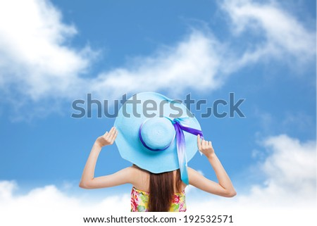 back of  girl holding a hat with blue sky background - stock photo