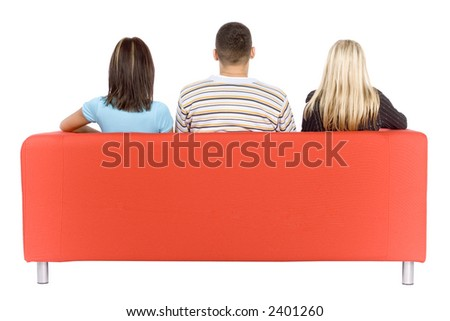 Back of man and two women sitting on a red couch.  Isolated on white background, in studio.