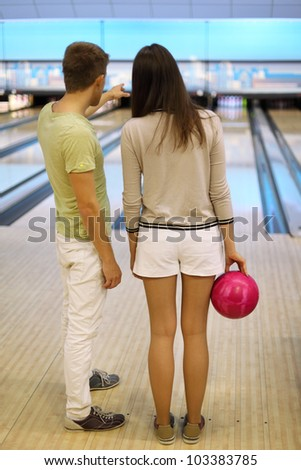 Back of man and woman with pink ball in bowling club; man shows bowling lane; shallow depth of field - stock photo
