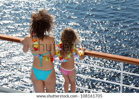 Back of mother and daughter dressed in swimsuits and garlands standing on deck of ship and looking at sea