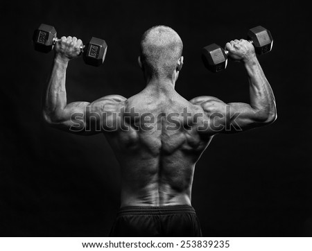 Back of muscular male bodybuilder with dumbbell - stock photo