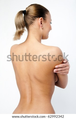 Back of nude beautiful girl on grey background. - stock photo