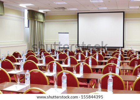 Back of red chairs and wooden tables with bottles and glasses in simple room for business meetings. - stock photo