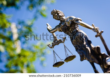 back of sculpture themis, femida or justice goddess on bright blue sky and green leaves outdoors background - stock photo