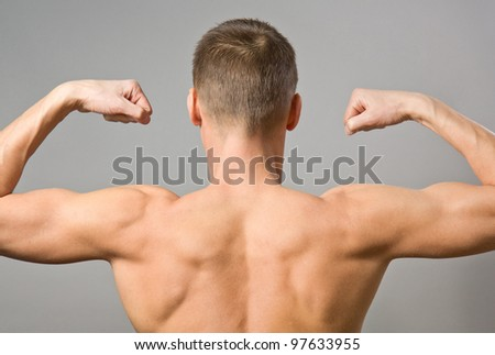 Back of sexy muscular man on a gray background - stock photo