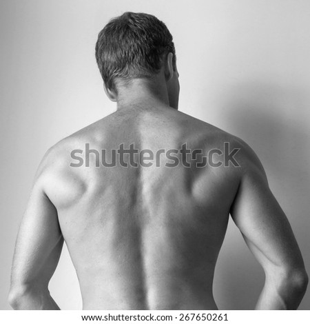 Back of Strong young Caucasian man, black and white studio photo - stock photo