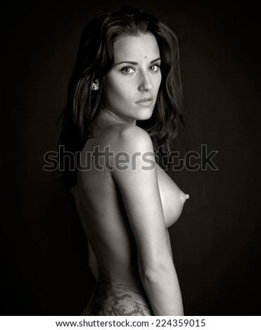 Back of the beautiful naked woman with tattoo. Photo with dark background. - stock photo