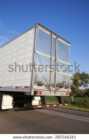 Back of the moving semi truck - stock photo