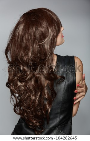 back of the woman with long brown curly hair with healthy shine, wearing a leather dress over a studio background.