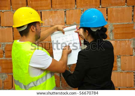 Back of two architects with blueprints working  on site,man pointing on project - stock photo