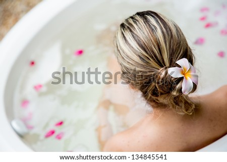 Back of woman in a bathtub and a flower in her hair - stock photo