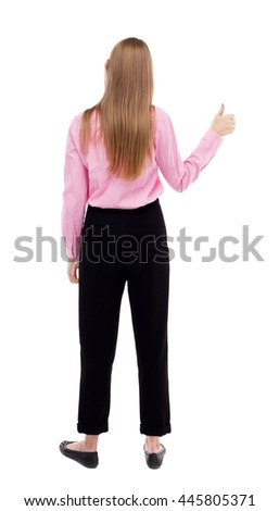 Back of  woman thumbs up. Rear people collection. backside view of person. Isolated over white background. The girl office worker in black trousers shows thumb up with his left hand. - stock photo