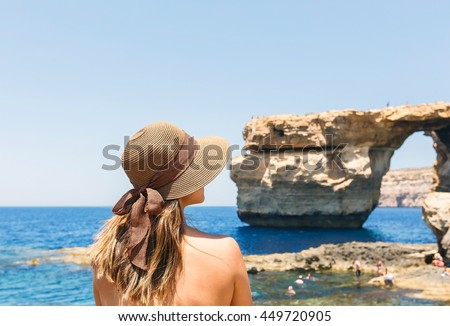 Back of woman wears hat, enjoys view of Azure window, famous tourist destination of Malta, Mediterranean sea - stock photo