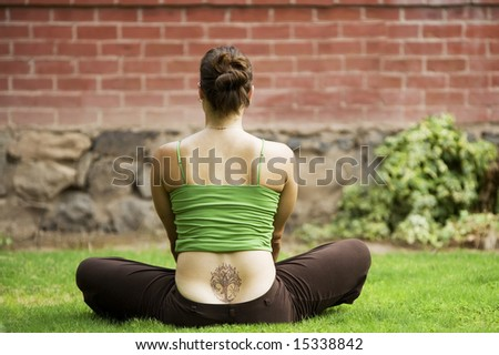 Back of woman with a tattoo sitting on grass - stock photo