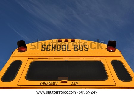 Back of Yellow School Bus with Blue Sky - stock photo