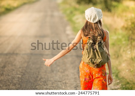 Back of young hipster woman with backpack - stock photo