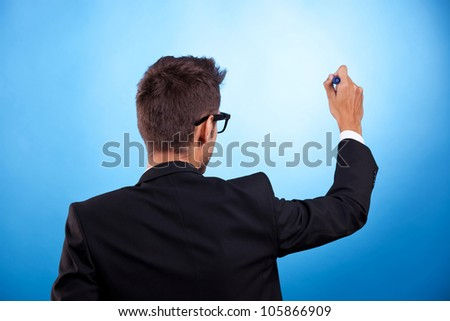Back of young man in a suit writing or drawing something on blue background - stock photo