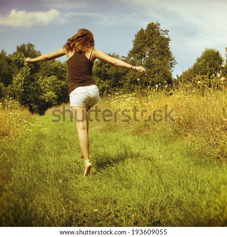 Back of young woman skipping down nature walk way, instagram filter style - stock photo