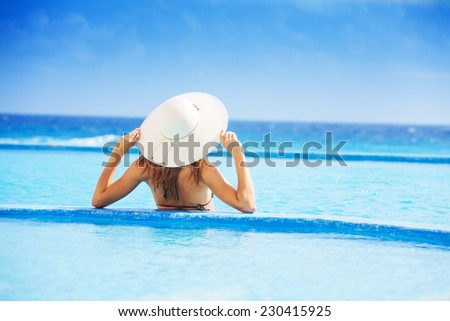 Back of young woman with white hat on the ocean coast during holidays summer time - stock photo