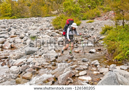 Back packing crossing a small stream in Nelson Lakes National Park in New Zealand - stock photo