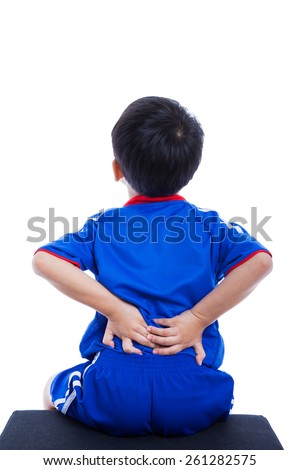 Back pain. Athlete little asian (thai) boy in blue sportswear rubbing the muscles of his lower back, cropped torso portrait, isolated on white background. Studio shot - stock photo