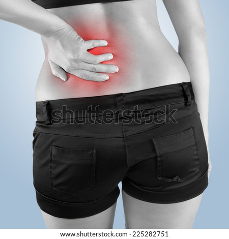Back pain. Athletic woman in black sportswear standing and rubbing the muscles of her lower back, cropped torso portrait. - stock photo