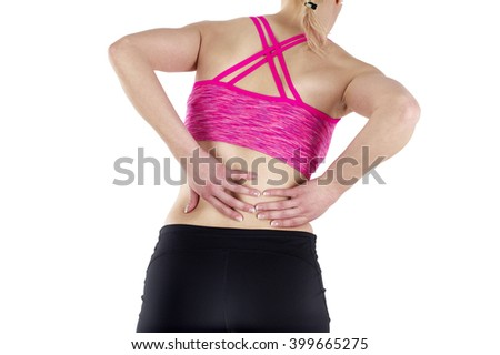 Back pain. Athletic woman in sports wear standing, rubbing the muscles of her lower back, cropped torso portrait. - stock photo