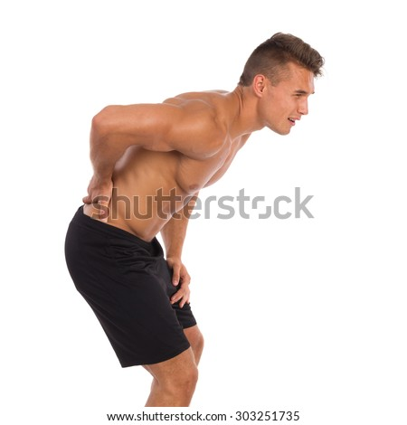 Back pain. Backache. Young muscular man in holding lower back in pain. Three quarter length studio shot isolated on white. - stock photo