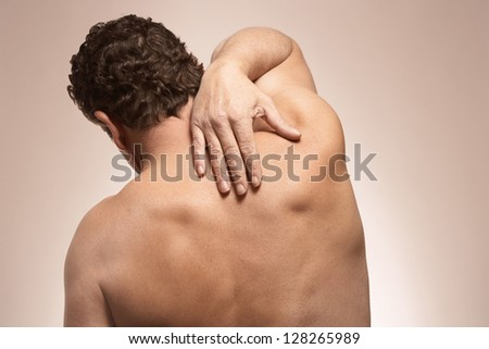 Back pain injury on fit adult man - stock photo