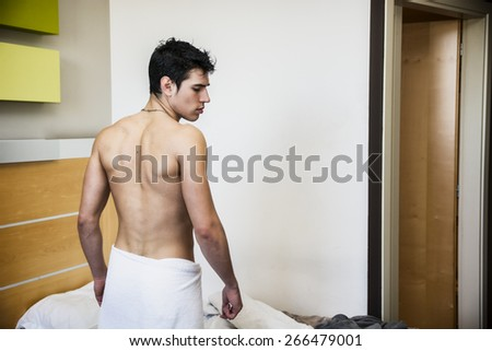 Back Portrait Of Handsome Young Shirtless Man Covered With Towel at Home in His Bedroom - stock photo
