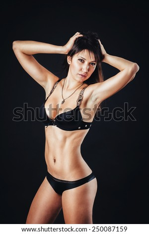 Back portrait of sexy woman posing in black lingerie over black background. The beautiful young sexy girl in stockings poses in studio on black background.fitness sports toned body. Bdsm Concept - stock photo