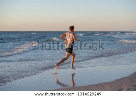 back portrait of young athletic fit and strong runner man training on Summer sunset beach in sea shore running and fitness workout in sport and healthy lifestyle concept