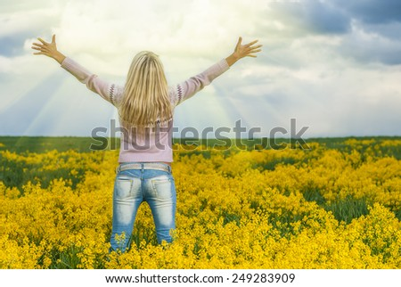 back portrait of young beautiful blonde outdoors. field and sky on background