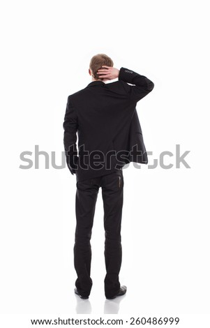 Back-pose of a corporate person thinking hard isolated over white background. Man in classic suit in a full-length standing with his back, one hand scratching his head. GUY in a black suit - stock photo