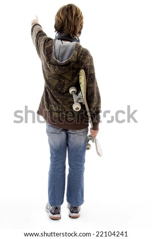 back pose of pointing boy holding skateboard on an isolated white background - stock photo