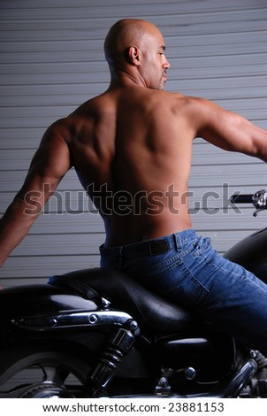 Back shot of a sexy muscular man sitting on a motor cycle, wearing jeans and no shirt.